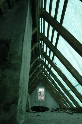 Ein Kran und fleißige Dachdecker